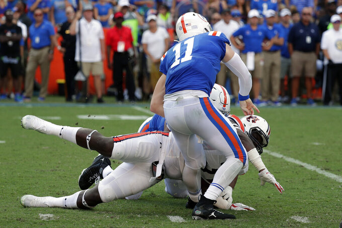 Florida quarterback Kyle Trask (11) is injured as he is hit by Auburn defensive end Marlon Davidson during the first half of an NCAA college football game, Saturday, Oct. 5, 2019, in Gainesville, Fla. (AP Photo/John Raoux)