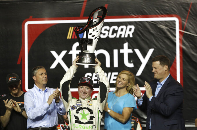 Tyler Reddick holds the trophy after winning the NASCAR Xfinity Series championship auto race at the Homestead-Miami Speedway, Saturday, Nov. 17, 2018, in Homestead, Fla. (AP Photo/Lynne Sladky)