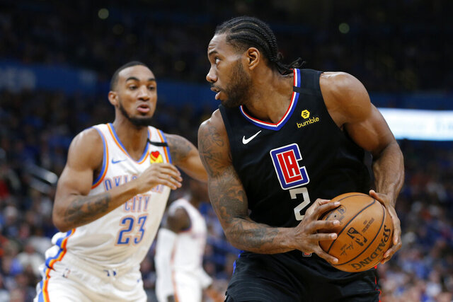 Los Angeles Clippers' Kawhi Leonard (2) goes against Oklahoma City Thunder's Terrance Ferguson (23) during the first half of an NBA basketball game in Oklahoma City, Tuesday, March, 3, 2020. (AP Photo/Garett Fisbeck)