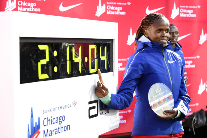 Brigid Kosgei of Kenya, poses with her time after winning the Women's Bank of America Chicago Marathon while setting a world record of 2:14:04, Sunday, Oct. 13, 2019, in Chicago. (AP Photo/Paul Beaty)