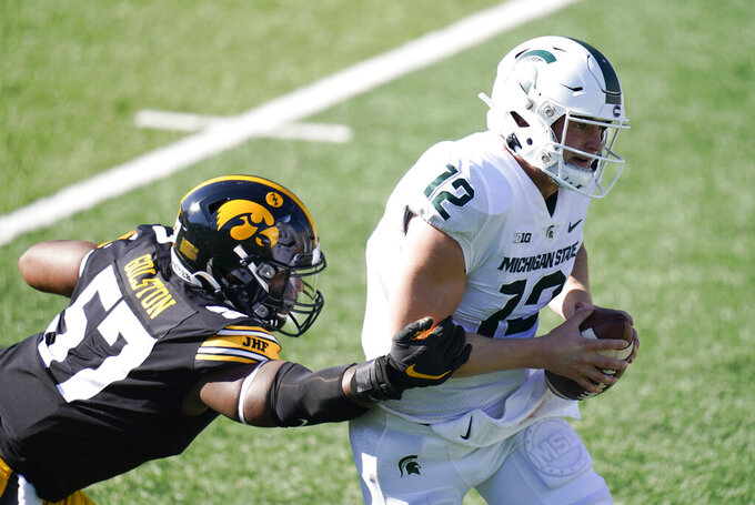 Michigan State quarterback Rocky Lombardi (12) runs from Iowa defensive lineman Chauncey Golston (57) during the first half of an NCAA college football game, Saturday, Nov. 7, 2020, in Iowa City, Iowa. (AP Photo/Charlie Neibergall)