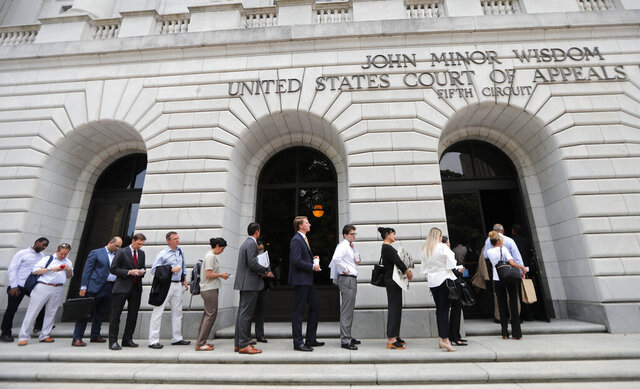 FILE - In this  July 9, 2019 file photo, people wait in line to enter the 5th Circuit Court of Appeals in New Orleans. On Wednesday, Feb. 26, 2020, the federal appeals court said the winner-take-all system Texas uses to assign Electoral College presidential votes is constitutional. Wednesday's ruling is the latest defeat for organizations that say each state's electors should be chosen proportionally, based on the percentage of the statewide vote.  (AP Photo/Gerald Herbert, File)