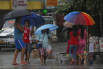 People walk through rain from passing Typhoon Kammuri on Tuesday, Dec. 3, 2019 in Subic, Philippines. The powerful typhoon was blowing across the Philippines on Tuesday after slamming ashore overnight in an eastern province, damaging houses and an airport and knocking out power after tens of thousands of people fled to safer ground. (AP Photo/Tatan Syuflana)