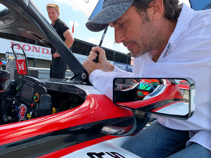Former IndyCar and NASCAR driver Michel Jourdain Jr. speaks with Salvador de Alba Jr., of Guadalajara, shown in mirror, during Indy Lights testing at the Mid-Ohio Sports Car Course in Lexington, Ohio. Just driving the Lights car for Andretti would have been enough to call his trip to Ohio a success. But de Alba had a fully immersive experience that went beyond his wildest dreams. (AP Photo/Jenna Fryer)