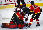 Arizona Coyotes' Nick Cousins, centre, crashes into Calgary Flames goalie Mike Smith, left, as Sean Monahan looks on during second period NHL hockey action in Calgary, Alberta, Monday, Feb. 18, 2019. (Jeff McIntosh/The Canadian Press via AP)