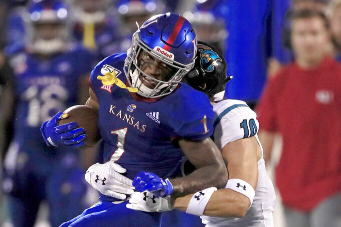 Kansas running back Pooka Williams Jr. (1) is tackled by Coastal Carolina safety Alex Spillum (10) during the second half of an NCAA college football game in Lawrence, Kan., Saturday, Sept. 7, 2019. (AP Photo/Orlin Wagner)