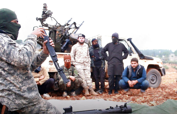 This photo released Tuesday, Nov. 13, 2018 by the al-Qaida-affiliated Ibaa News Agency, shows al-Qaida-linked militants learning how to use a heavy weapon in the countryside of Idlib, Syria. It took HTS militants only few days to capture more than two dozen towns and villages in and around Idlib province, cementing the group's control over an area in northwestern Syria the size of neighboring Lebanon. The push  is the most serious blow to a September cease-fire for Idlib brokered by Russia and Turkey. (Ibaa News Agency, via AP)