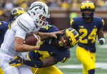 Western Michigan quarterback Jon Wassink, left, is tackled by Michigan defensive back Josh Metellus (14) in the second quarter of an NCAA college football game in Ann Arbor, Mich., Saturday, Sept. 8, 2018. (AP Photo/Tony Ding)