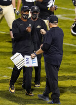 Colorado head coach Karl Dorrell, left, greets UCLA head coach Chip Kelly after the second half of an NCAA college football game Saturday, Nov. 7, 2020, in Boulder, Colo. (AP Photo/David Zalubowski)
