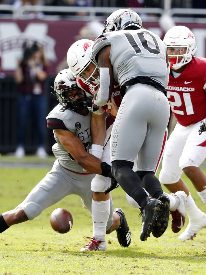 Arkansas quarterback Ty Storey (4) fumbles the ball after being double-teamed by Arkansas defensive back Jayden Minchew (38) and defensive lineman Randy Ramsey (10) during the first half of an NCAA college football game in Starkville, Miss., Saturday, Nov. 17, 2018. Mississippi State won 52-6. (AP Photo/Rogelio V. Solis)
