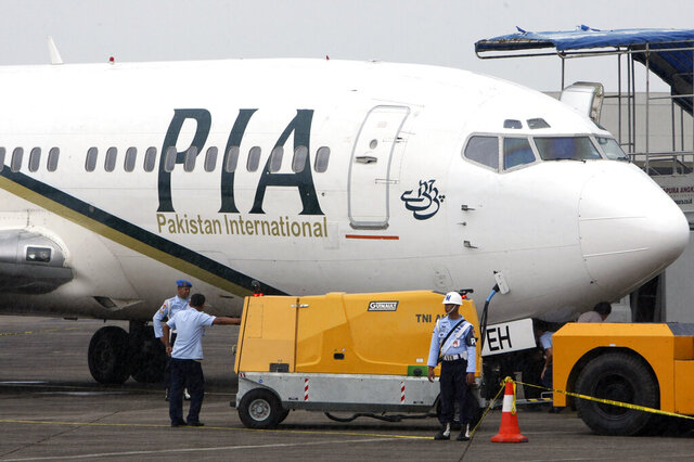 FILE - In this March 7, 2011 file photo, a Pakistan International Airlines passenger jet is parked on the tarmac at a military base in Makassar, Indonesia. The spokesman of Pakistan's national carrier said Wednesday, July 8, 2020, that the airline is firing 28 pilots found to have tainted licenses, the latest chapter in a scandal that emerged in the wake of the Airbus A320 crash in Karachi in May. An inquiry into the crash, which killed 97 people on board, resulted in the stunning revelation that 260 of 860 pilots in Pakistan had cheated on their pilots exams, but were still given licences by the Civil Aviation Authority. (AP Photo, File)