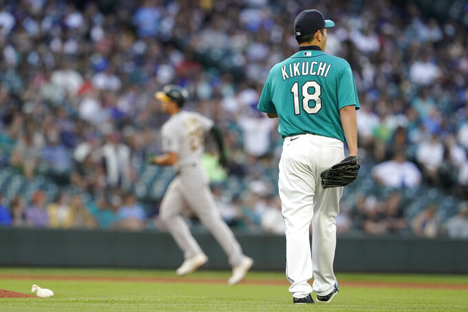 Seattle Mariners starting pitcher Yusei Kikuchi (18) waits as Oakland Athletics' Matt Olson, left, rounds the bases after hitting a solo home run during the fourth inning of a baseball game Friday, July 23, 2021, in Seattle. (AP Photo/Ted S. Warren)