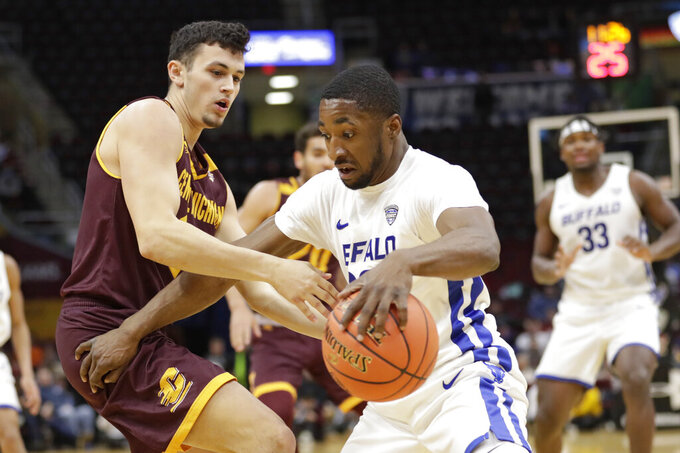 Buffalo's Dontay Caruthers, right, drives past Central Michigan's Matt Beachler during the first half of an NCAA college basketball game in the semifinals of the Mid-American Conference men's tournament Friday, March 15, 2019, in Cleveland. (AP Photo/Tony Dejak)