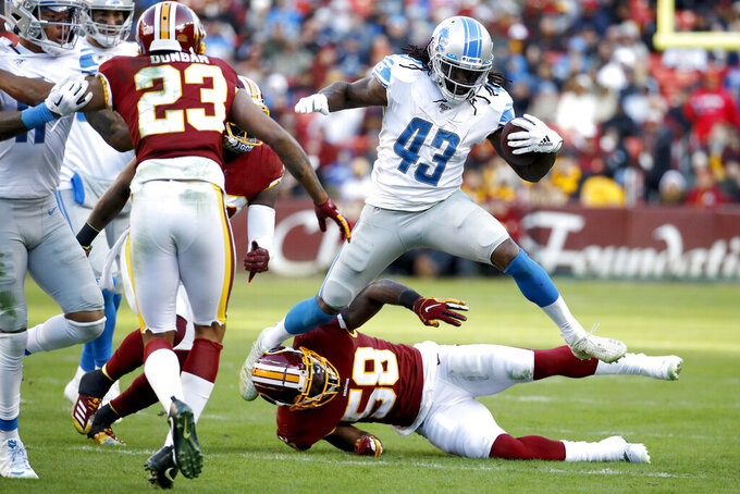 Detroit Lions running back Bo Scarbrough (43) jumps over Washington Redskins linebacker Carroll Phillips (58) while running with the ball during the second half of an NFL football game, Sunday, Nov. 24, 2019, in Landover, Md. (AP Photo/Patrick Semansky)