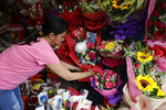 Shop owner Mary Jane Villegas arranges a Valentines flower arrangement which they called