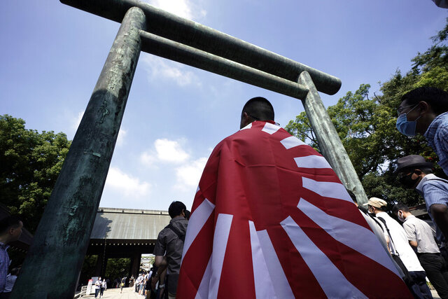 Visitors queue to enter Yasukuni Shrine Saturday, Aug. 15, 2020, in Tokyo. Japan marked the 75th anniversary of the end of World War II. (AP Photo/Eugene Hoshiko)