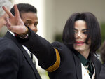 FILE - In this March 2, 2005, file photo, pop icon Michael Jackson waves to his supporters as he arrives for his child molestation trial at the Santa Barbara County Superior Court in Santa Maria, Calif. A California appeals court is strongly inclined to give new life to lawsuits filed by two men who accuse Michael Jackson of molesting them when they were boys. In a tentative ruling Monday, the 2nd District Court of Appeal said lawsuits from James Safechuck and Wade Robson should be reconsidered by the trial court that dismissed them in 2017. The decision is based on a new California law that gives sex abuse victims far longer to sue. (AP Photo/Michael A. Mariant, File)