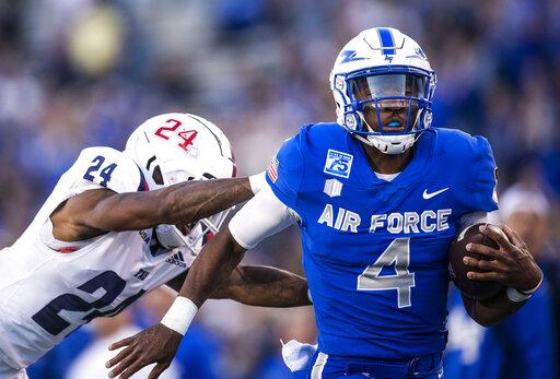Air Force quarterback Haaziq Daniels (4) dodges Florida Atlantic cornerback Zyon Gilbert (24) as he runs in for a touchdown during an NCAA college football game at Air Force Academy, Colo., on Saturday, Sept. 25, 2021. (Chancey Bush/The Gazette via AP)