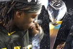 Oregon cornerback Haki Woods Jr. (14) kisses the trophy after Oregon defeated Utah 37-15 in an NCAA college football game for the Pac-12 Conference championship in Santa Clara, Calif., Friday, Dec. 6, 2018. (AP Photo/Tony Avelar)