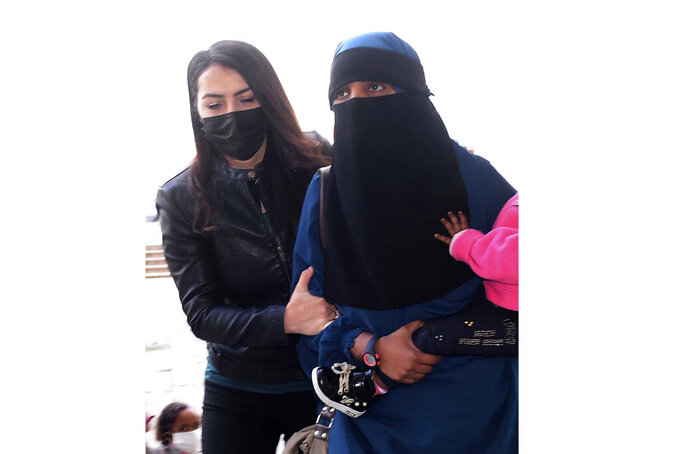 FILE - In this Feb. 15, 2021, file photo, a woman, who was identified only by her initials S.A., one of three New Zealand nationals, is escorted by a Turkish police officer, left, to the local courthouse in Hatay, Turkey. New Zealand on Monday, July 26, 2021 agreed to repatriate the alleged Islamic State militant and her two young children, who have been detained in Turkey since February. (DHA via AP, File)