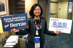 "Una Lee Jost, a lawyer from Pasadena, Calif., holds signs supporting Bernie Sanders at the California Democratic Convention in Long Beach, Calif., Saturday, Nov. 16, 2019. She says any delay in ""Medicare for All"" is a ""serious concern"" after Sen. Elizabeth Warren announced that getting Congress to pass a fully government-funded, universal health coverage plan would likely not come until the third year of her administration. (AP Photo/Michael R. Blood)"