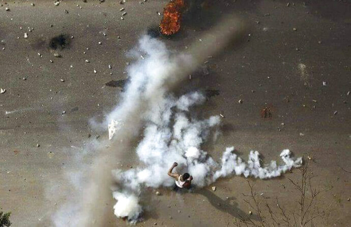FILE - In this Dec. 21, 2018 file handout photo provided a Sudanese activist, a protester stands in tear gas during clashes with security forces in Khartoum, Sudan. The anti-government protests rocking Sudan for the past month are reminiscent of the Arab Spring uprisings of nearly a decade ago. Demonstrators, many in their 20s and 30s, are trying to remove President Omar al-Bashir, an authoritarian leader, and win freedoms and human rights. (Sudanese Activist via AP, File)