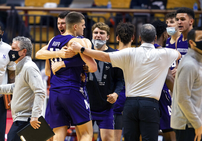 Northwestern forward Robbie Beran (31) and forward Miller Kopp (10) react with their teammates after defeating Indiana in an NCAA college basketball game, Wednesday, Dec. 23, 2020, in Bloomington, Ind. Northwestern won 74-67. (AP Photo/Doug McSchooler)