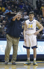 West Virginia head coach Bob Huggins gives instructions to forward Logan Routt (31) during the first half of an NCAA college basketball game Monday, Feb. 12, 2018, in Morgantown, W.Va. (AP Photo/Raymond Thompson)
