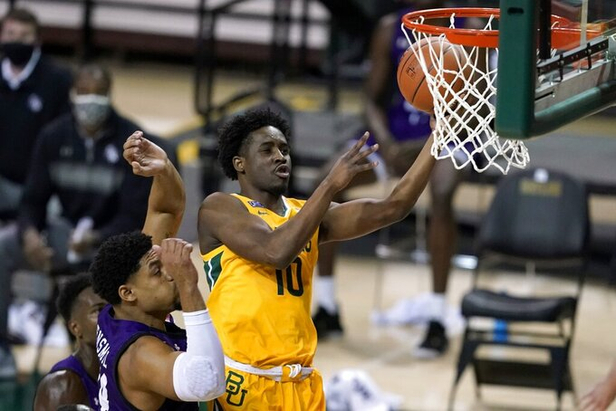 Baylor guard Adam Flagler (10) goes up for a shot over Stephen F. Austin forward Gavin Kensmil, left, during the first half of an NCAA college basketball game in Waco, Texas, Wednesday, Dec. 9, 2020. (AP Photo/Tony Gutierrez)