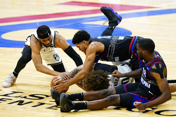 Brooklyn Nets' Bruce Brown, left, and Iman Shumpert, middle, battle for a loose ball with Philadelphia 76ers' Tobias Harris, top, and Shake Milton, right, during the first half of an NBA basketball game, Saturday, Feb. 6, 2021, in Philadelphia. (AP Photo/Matt Slocum)