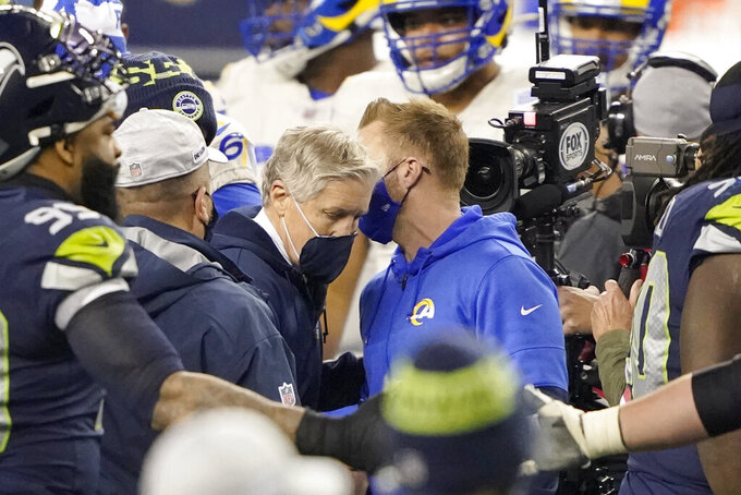 Seattle Seahawks head coach Pete Carroll, left, greets Los Angeles Rams head coach Sean McVay after an NFL wild-card playoff football game, Saturday, Jan. 9, 2021, in Seattle. (AP Photo/Ted S. Warren)