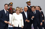 From the left, Dutch Prime Minister Mark Rutte, German Chancellor Angela Merkel, Portugal's President Marcelo Rebelo de Sousa and French President Emmanuel Macron, attend Bastille Day parade Sunday, July 14, 2019 on the Champs Elysees avenue in Paris. (AP Photo/Kamil Zihnioglu)