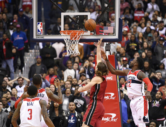 Miami Heat forward Kelly Olynyk, second from right, puts up a shot against Washington Wizards forward Jeff Green (32) during the closing seconds of the second half of an NBA basketball game, Thursday, Oct. 18, 2018, in Washington. Also seen are Wizards guard Bradley Beal (3) and forward Markieff Morris, second from left. The Heat won 113-112. (AP Photo/Nick Wass)