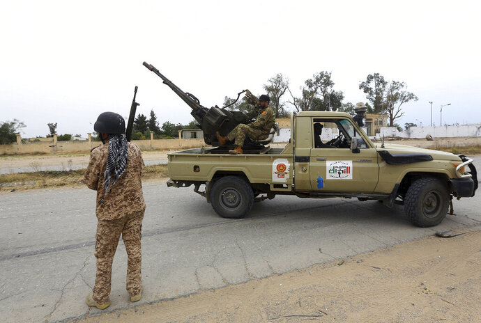FILE - In this May 21, 2019 file photo, Tripoli government forces clash with forces led by Field Marshal Khalifa Hifter, south of the capital Tripoli, Libya. Turkey is secretly expanding its footprint in conflict-ridden Libya, fueling the country's civil war and deepening fault lines with Mediterranean neighbors and between international allies. Turkey seems to be after lucrative construction and port contracts, according to Libyan officials. (AP Photo/Hazem Ahmed, File)