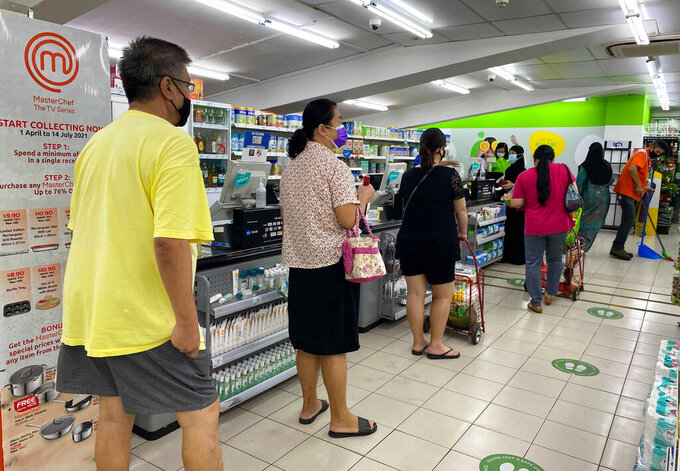People wear masks and observe social distancing while lining up to pay at a supermarket in Singapore, Friday, May 14, 2021. Singapore further tightened its COVID-19 measures as it sought to control an increase in untraceable coronavirus infections in the city-state. (AP Photo/Zen Soo