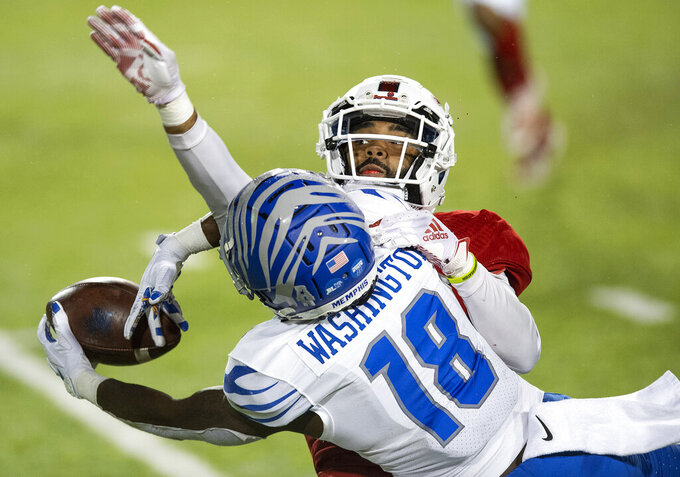 Memphis wide receiver Tahj Washington (18) makes a reception against Florida Atlantic cornerback Diashun Moss during the Montgomery Bowl NCAA college football game in Montgomery, Ala., Wednesday, Dec. 23, 2020. (Mickey Welsh/The Montgomery Advertiser via AP)