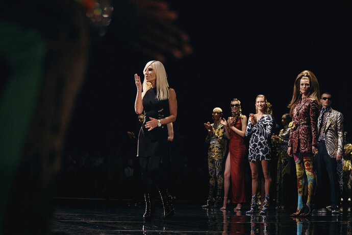 FILE - IN THIS  Dec. 2, 2018 file photo, Donatella Versace salutes during the Versace fashion show in New York. Gianni Versace's entrance into the fashion group owned by American designer Michael Kors was finalized last week. The Milan Fashion Week devoted to fall and winter menswear opens on Friday. (AP Photo/Andres Kudacki)
