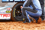 A crew member checks tire pressure on a truck as they prepare to compete in a heat race for a NASCAR Truck Series race on Saturday, March 27, 2021, in Bristol, Tenn. (AP Photo/Wade Payne)