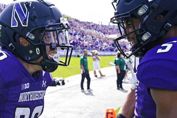 Northwestern running back Evan Hull, left, smiles as he celebrates with wide receiver Stephon Robinson Jr. after scored a touchdown during the first half of an NCAA college football game against Ohio in Evanston, Ill., Saturday, Sept. 25, 2021. (AP Photo/Nam Y. Huh)