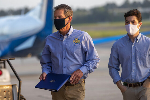 Gov. Brian Kemp, left, is briefed by his press aid Tate Mitchell, right, before speaking at a press conference in a hanger at the DeKalb-Peachtree Airport in Atlanta, Friday, Sept. 4, 2020.  Kemp and first lady Marty Kemp will take part in a fly-around tour of Georgia. (Alyssa Pointer/Atlanta Journal-Constitution via AP)