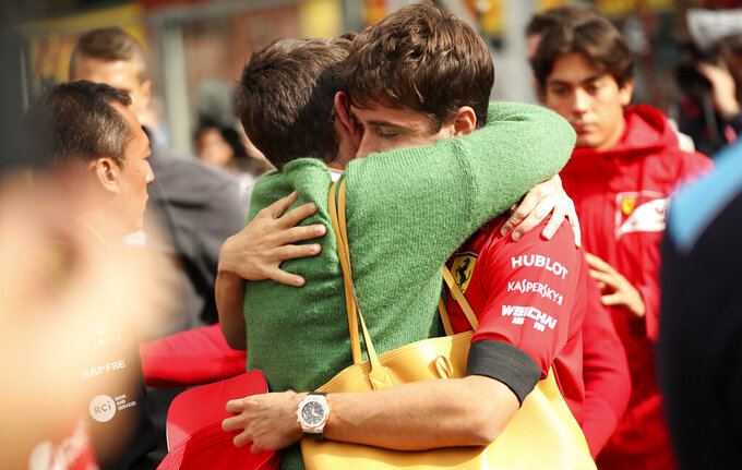 The mother of Anthoine Hubert embraces Ferrari driver Charles Leclerc of Monaco after a moment of silence for Formula 2 driver Anthoine Hubert at the Belgian Formula One Grand Prix circuit in Spa-Francorchamps, Belgium, Sunday, Sept. 1, 2019. The 22-year-old Hubert died following an estimated 160 mph (257 kph) collision on Lap 2 at the high-speed Spa-Francorchamps track, which earlier Saturday saw qualifying for Sunday's Formula One race. (AP Photo/Francisco Seco)
