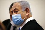 Israeli Prime Minister Benjamin Netanyahu, wearing a face mask in line with public health restrictions due to the coronavirus pandemic, stands inside the court room as his corruption trial opens at the Jerusalem District Court, Sunday, May 24, 2020.  He is the country's first sitting prime minister ever to go on trial, facing charges of fraud, breach of trust, and accepting bribes in a series of corruption cases stemming from ties to wealthy friends. (Ronen Zvulun/ Pool Photo via AP)