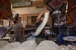 In this May 9, 2020 photo, 28-year-old football defender Mahrous Mahmoud, right, makes Ramadan sweets, in Manfalut, a town 350 kilometers (230 miles) south of Cairo in the province of Assiut, Egypt. Mahmoud should be on the field at this time of year playing as a defender for Beni Suef, a club in Egypt's second division. But like millions in the Arab world's most populous country, he has been hit hard by the coronavirus pandemic. (AP Photo/Nariman El-Mofty)
