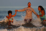 Eddie Miranda and his daughters, Niya, left, and Eva frolic in threw surf Wednesday, Aug. 5, 2020, at Old Orchard Beach, Maine. The family, from West Hartford, Conn., is vacationing in the Maine which ranks one of the lowest in the nation in positive cases of coronavirus. (AP Photo/Robert F. Bukaty)