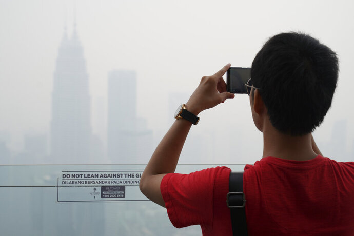 Tourist take a picture from Kuala Lumpur Tower as city stands shrouded with haze in Kuala Lumpur, Malaysia, Friday, Sept. 13, 2019. Malaysian authorities plan to conduct cloud-seeding activities to induce rain to ease the haze. The government said it will press Jakarta to take immediate action to put out the burning forests and ensure the fires won't occur again. (AP Photo/Vincent Thian)