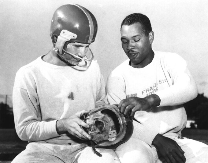 FILe - In this, San Francisco 49ers fullback Joe Perry, right, shows quarterback Y. A. Tittle the plastic mask he has worn during the football season to protect his bridgework, during practice at Menlo Park, Calif. Tittle, who suffered a cheekbone fracture against the Detroit Lions, is wearing the mask he has used since. Helmets have evolved from the original hard leather of the NFL's infancy to hard polycarbonate single-piece shells with various amounts of padding and air bladders that served as the primary form of head protection into the beginning of this century.  (AP Photo/File)
