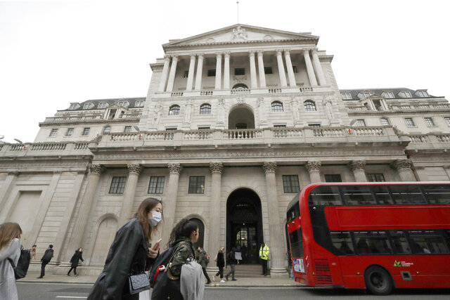 FILE - In this file photo dated Wednesday, March 11, 2020, Pedestrians wearing face masks pass the Bank of England in London.  In forecasts published Thursday May 7, 2020, The Bank of England has warned that the British economy could be nearly a third smaller by the end of the first half of this year as a result of the coronavirus pandemic, but also notes the economy could revive quickly. (AP Photo/Matt Dunham, FILE)