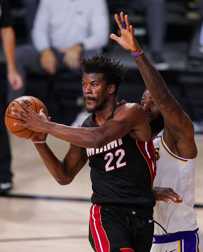 Miami Heat's Jimmy Butler (22) passes the ball against Los Angeles Lakers' LeBron James (23) during the second half in Game 3 of basketball's NBA Finals, Sunday, Oct. 4, 2020, in Lake Buena Vista, Fla. (AP Photo/Mark J. Terrill)