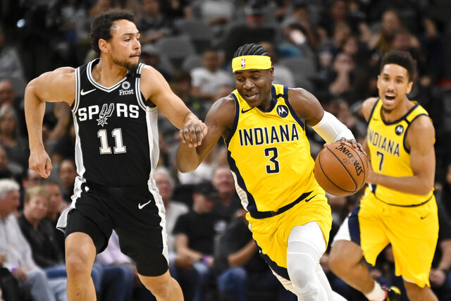 Indiana Pacers' Aaron Holiday (3) drives against San Antonio Spurs' Bryn Forbes during the first half of an NBA basketball game, Monday, March 2, 2020, in San Antonio. (AP Photo/Darren Abate)