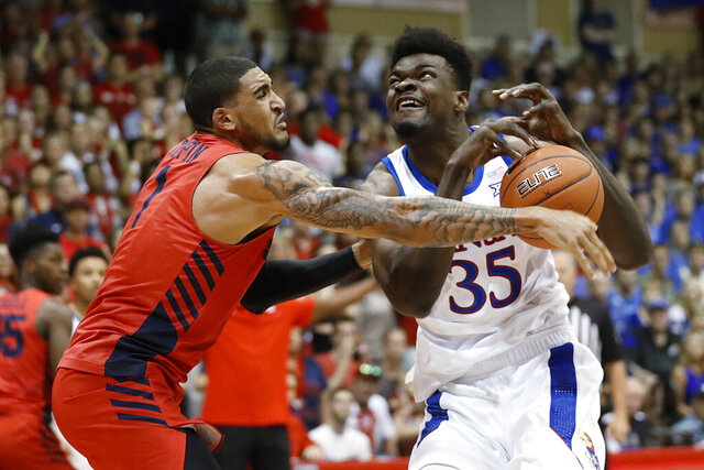 FILE - In this Nov. 27, 2019, file photo, Dayton forward Obi Toppin (1) knocks the ball away from Kansas center Udoka Azubuike (35) during the first half of an NCAA college basketball game in Lahaina, Hawaii. Kansas and Dayton were headed toward earning No. 1 seeds in the NCAA tournament, so any meeting would have to be in the Final Four or national championship game. What a rematch it would be. The Jayhawks and Flyers played a high-level game at the Maui Invitational, won 90-84 in overtime by Kansas. (AP Photo/Marco Garcia, File)